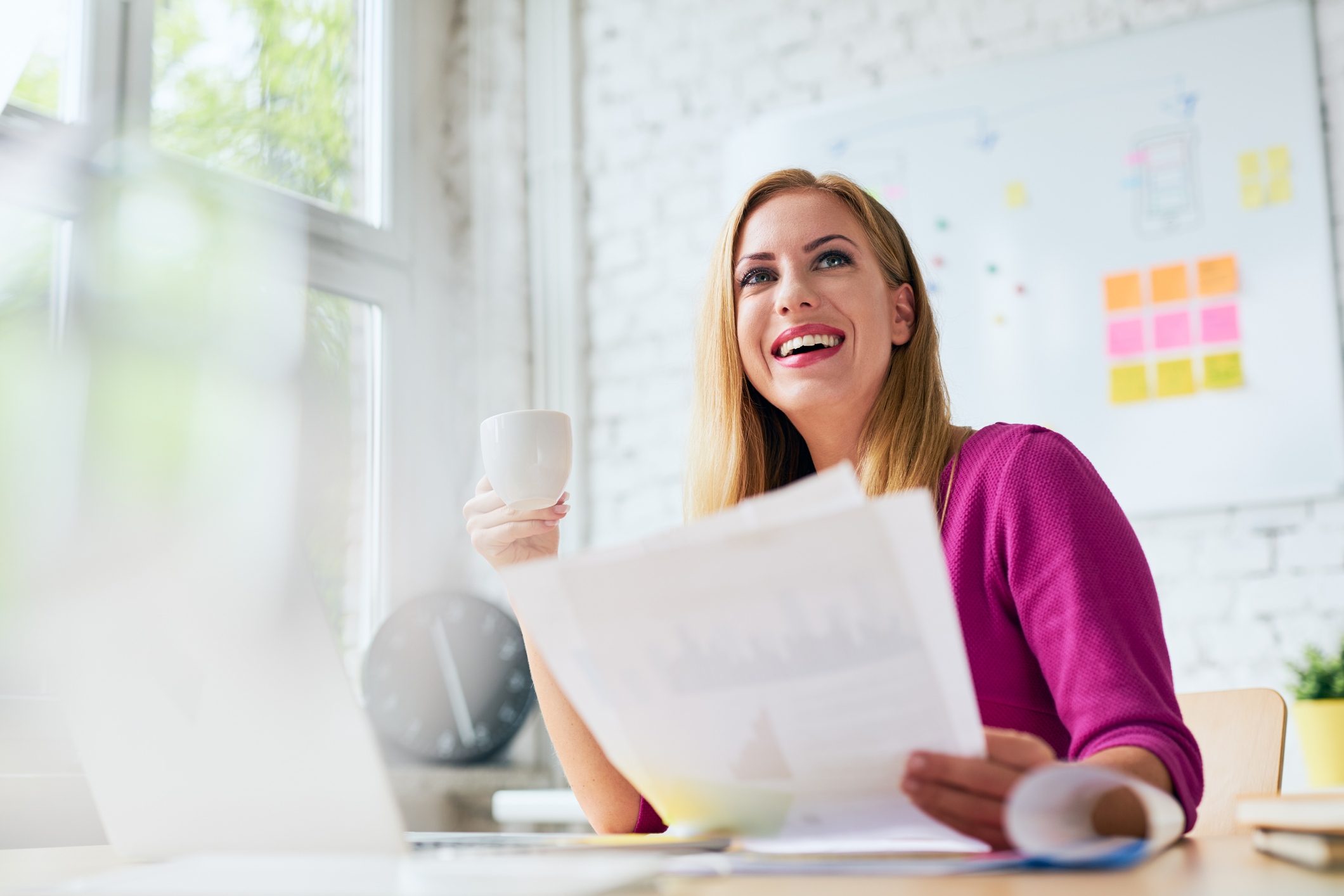 woman smiling while reviewing reports and drinking coffee